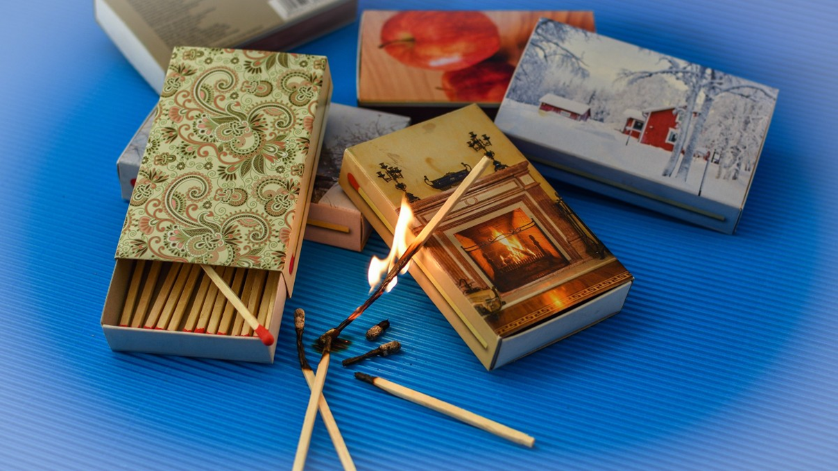 Matchboxes with various coves and a lit match