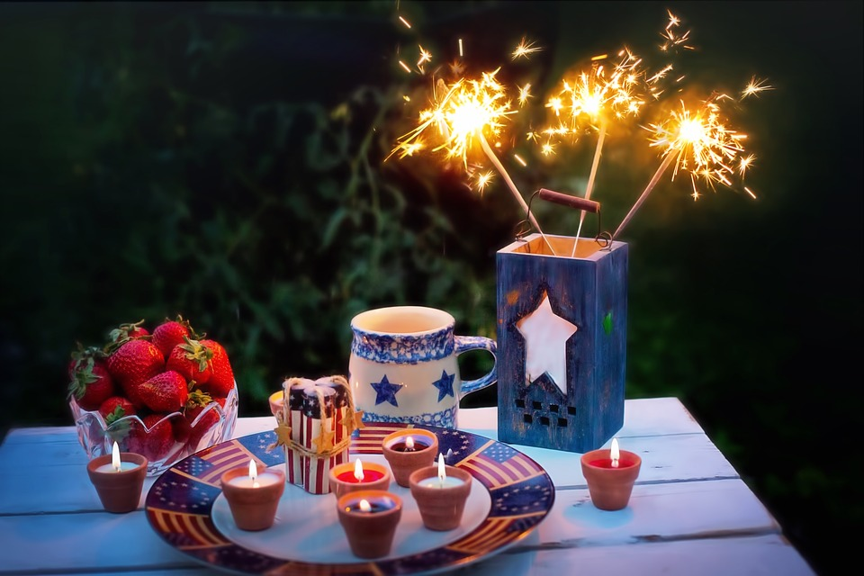 Candles and lit sparklers next to tea mug and strawberries