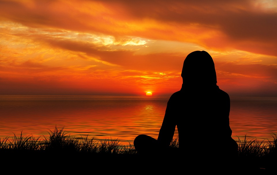 woman's silhouette sitting in front of sunset
