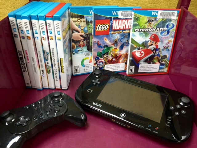 a WiiU video gaming console and controller with a pile of Wii video games beside it.