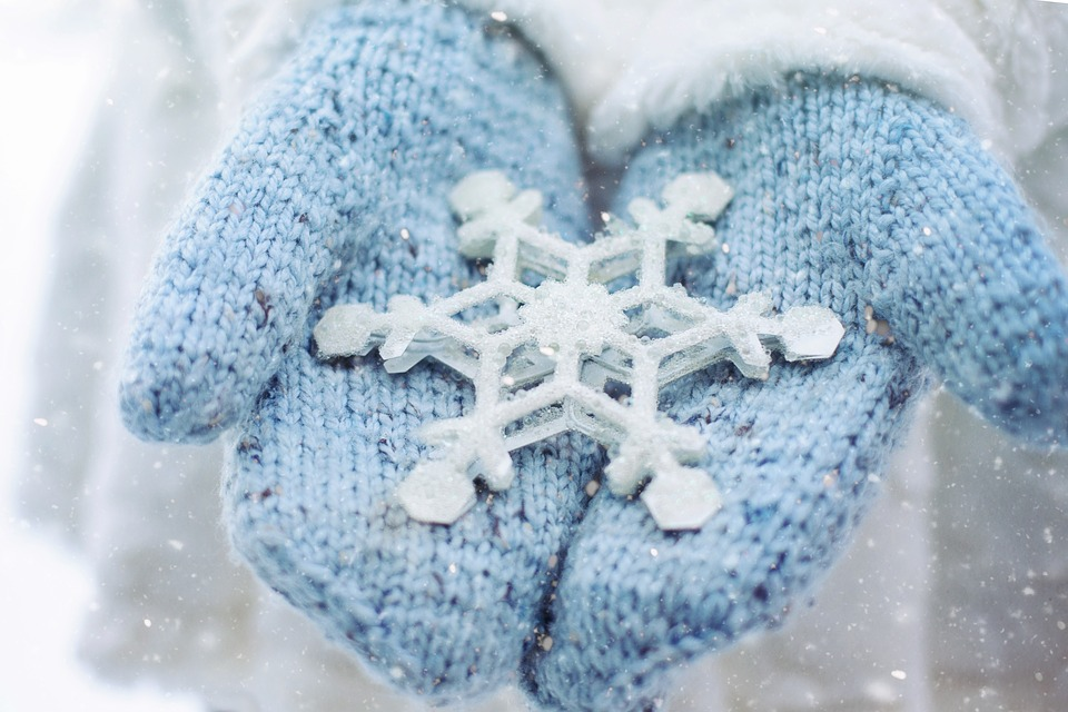 Mittened hands holding large snow flake