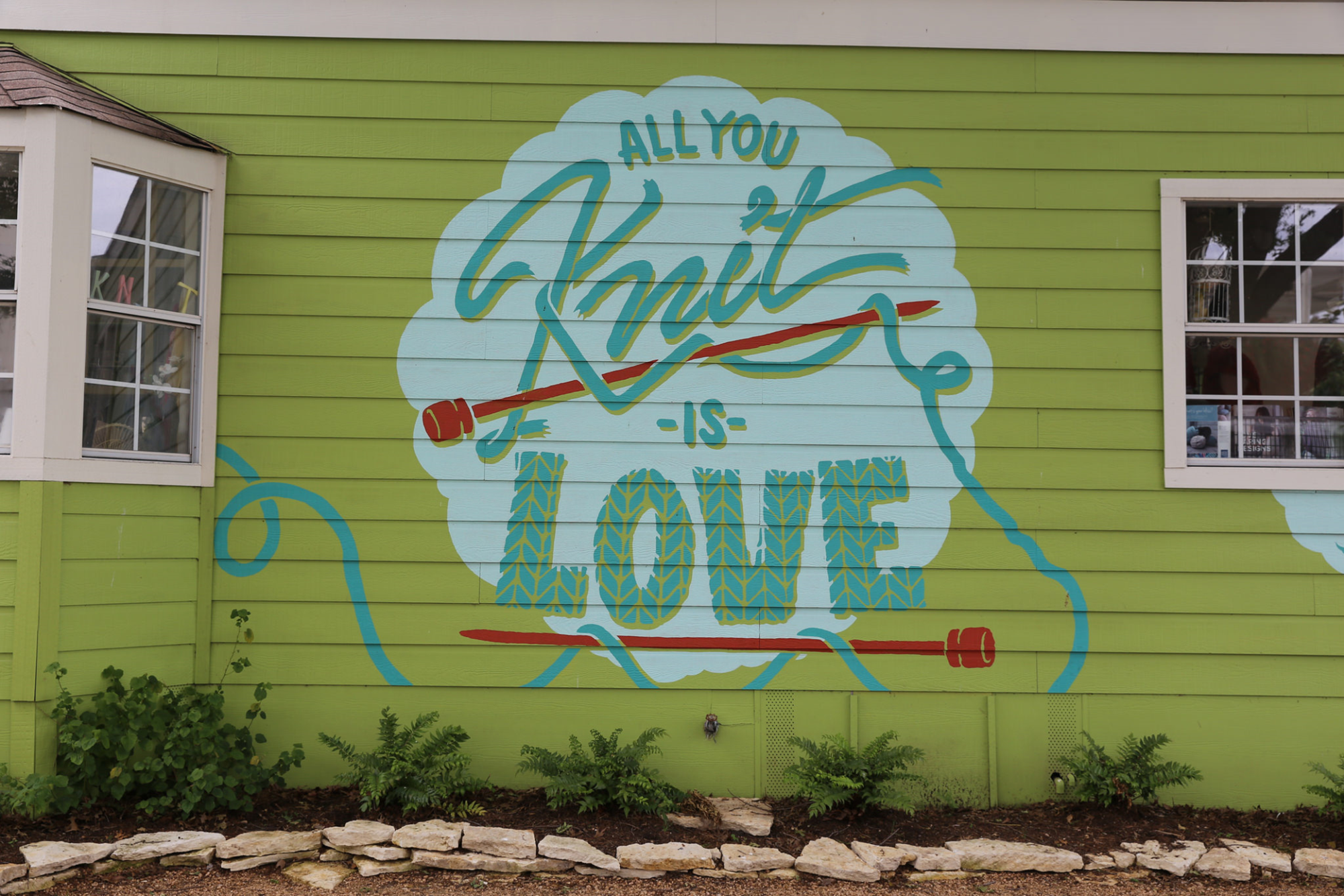 "Painted sign on wall says ""All you knit is love"""