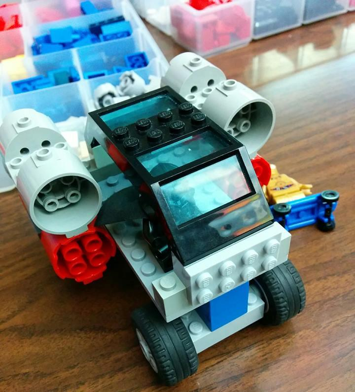 a truck made out of lego toys, with more legos in clear containers in the background